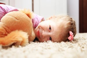 Happy little girl lying on soft ca