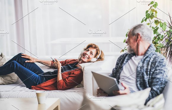 Senior Couple With Tablet And Smartphone Relaxing At Home