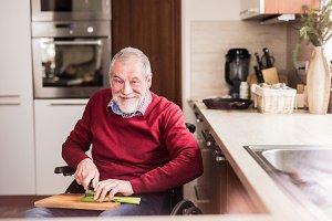Senior man in wheelchair cooking in the kitchen.