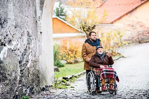 Senior father in wheelchair and young son on a walk.