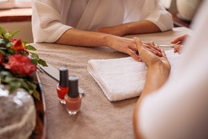 Manicurist shaping female clients