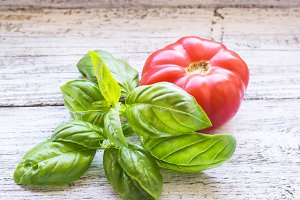 Tomato and basil on white wooden background.