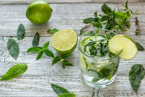 Mojito cocktail with lime and mint in highball glass on a white wooden background