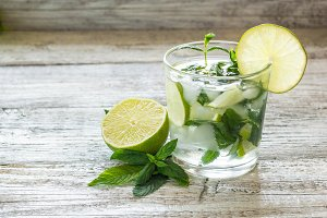 Mojito cocktail with lime and mint in highball glass on a white wooden background Copy space