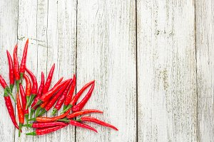 frame of red Chile pepper on white wooden table