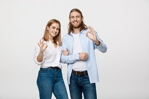 Happy young couple doing Ok gesture, isolated on white background