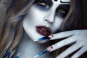 Portrait of a horrible scary Corpse Bride in wreath with dead flowers, halloween makeup and long manicure.Design of nails