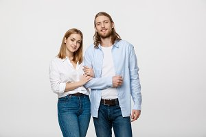 Portrait of attractive young couple smiling for the camera while holding arm to arm. On grey background.