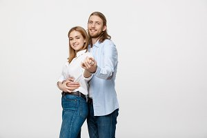 Young elegant couple in casual cloth dancing over Isolated on white studio background.