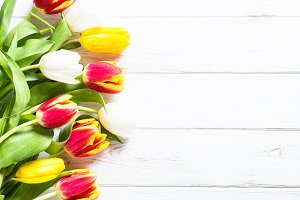 Red yellow and white tulips on white wooden table.