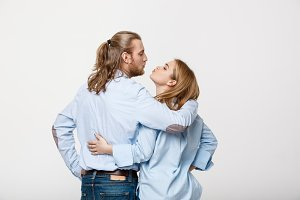 Young caucasian couple kissing over isolated white studio background.