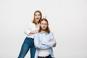 Portrait of lovely young couple showing peace or victory sign on white studio background