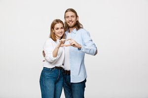 Valentine Couple - portrait of smiling Beauty Girl and her Handsome Boyfriend making shape of Heart by their Hands.