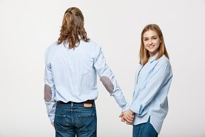 happy loving couple holding hands over white background