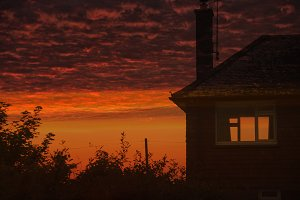 Dramatic red sunset and house