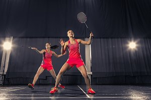 Young women playing badminton at gym