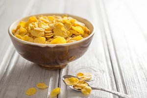 Bowl with cornflakes on white wooden