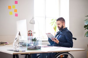 Businessman in wheelchair with tablet in his office.