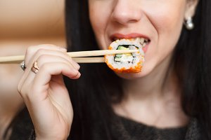Young woman in wig eating sushi by c