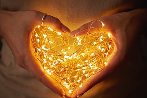 Woman holding lights in the shape of a heart