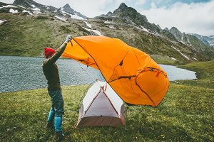 Man pitching tent camping outdoor