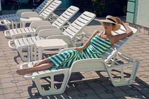 girl lies on a chaise longue in a green striped dress