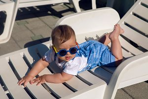 child in a denim suit and sunglasses lying