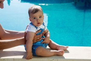 baby boy sitting by the pool