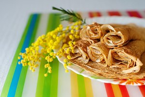 Stack of Russian-style pancakes and a branch of a blossoming mimosa. Spring. Maslenitsa