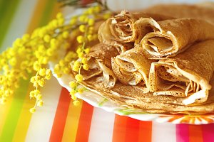 Closeup image of golden pancakes over colorful background
