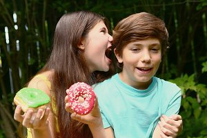 teenager siblings brother and sister with doughnuts