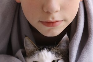 teen boy with cat wrap in rug