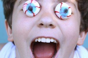 teenager boy with candy eyes close up grimacing open mouth