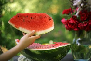 big ripe water melon with hand hold slice