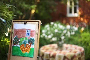 artist hand painting picture of jasmin flowers and cottage house