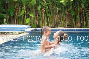 Happy mother and her daughter have fun in swimming pool
