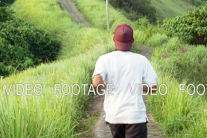Young men running over green hill over jungle forest background. trail of artists