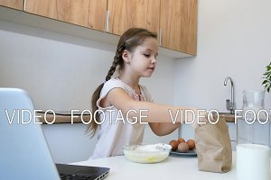 little girl learns to cook in the kitchen and make bakery using laptop