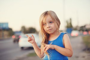 Little girl stands at highway