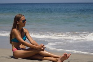 Girl in the sun glasses sits on the beach.