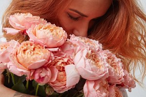 pretty girl holding a bouquet of pink roses