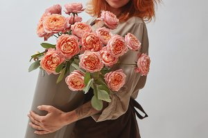girl holding a vase with a bouquet of roses