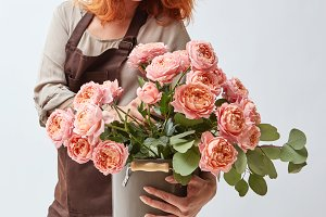 Woman holding a vase with fresh pink roses