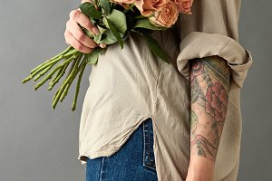 Woman in blue jeans with a bouquet of beige roses