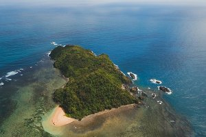 Seascape with tropical island, beach, rocks and waves. Catanduanes, Philippines.