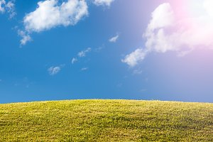Green grassy lawn or meadow with blue sky and sun flare