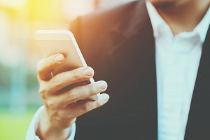 Close-up smart Business man wearing modern black suit and white shirt and texting on mobile smart phone with flare light