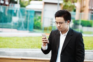 Concept Business - Business man serious with his project on his mobile phone
