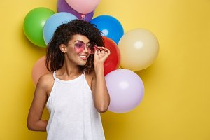 Celebration Concept - Close up Portrait happy young beautiful african woman with white t-shirt smiling with colorful party balloon. Yellow Pastel studio Background