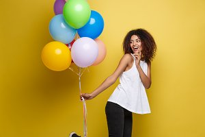 Celebration Concept - Close up Portrait happy young beautiful african woman with white t-shirt running with colorful party balloon. Yellow Pastel studio Background